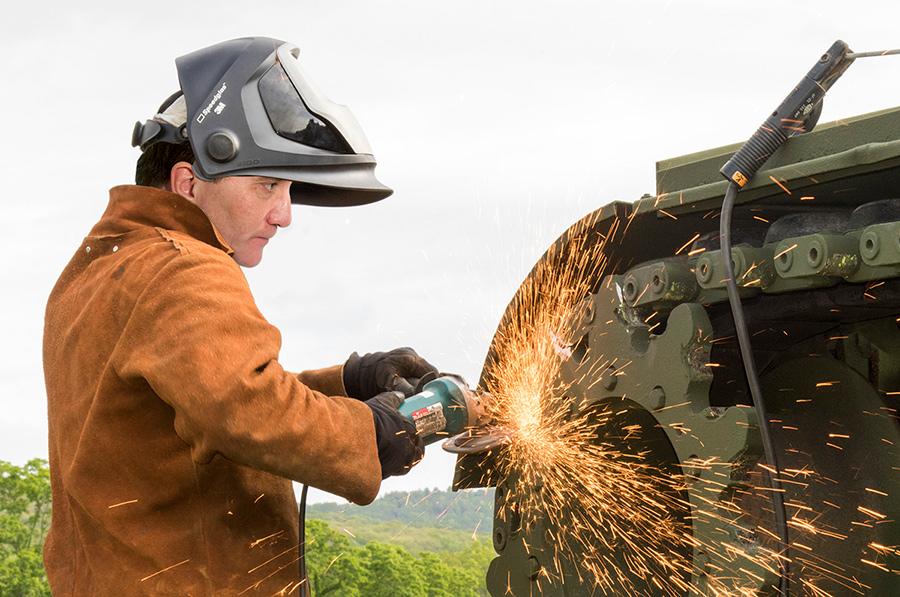 Svetsaren Stefan Löfven går på med kantslipen på en bandvagn - Montage på foton av Sgt. Michael Davis, New York National Guard via Flickr.com och TT.se