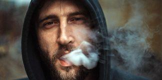 Rökande man med huva. Foto: Vadim Kaipov. Licens: Unsplash.com