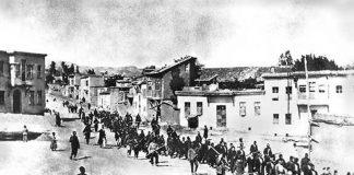 Civila armenier förs till ett närbeläget fängelse i Mezireh av beväpnade turkiska soldater. Kharpert, Osmanska riket, april 1915. Licens: Public Domain